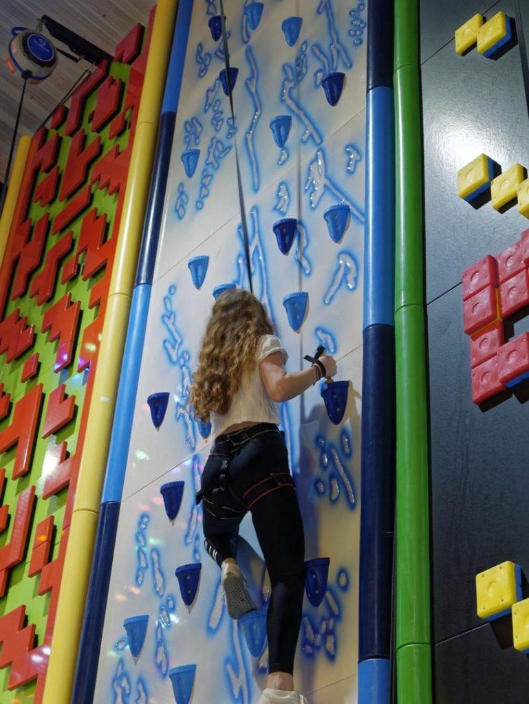 femme grimpant un mur d'escalade