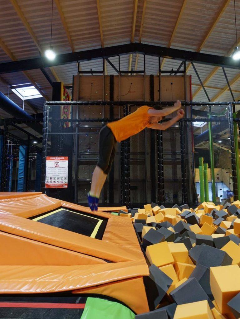 Homme qui saute d'un trampoline dans la mousse