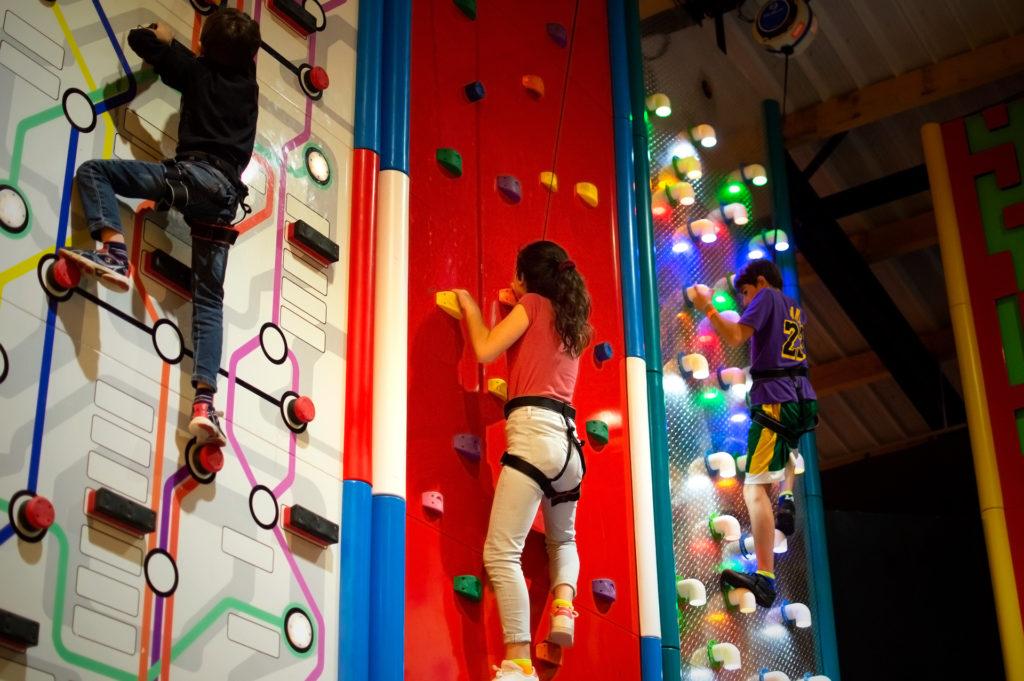 enfant sur un mur d'escalade rouge